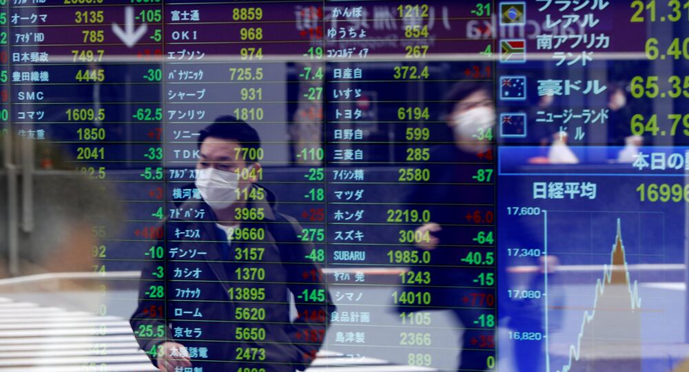 Passersby wearing protective face masks following an outbreak of the coronavirus disease (COVID-19) are reflected on a screen displaying stock prices outside a brokerage in Tokyo, Japan, March 17, 2020