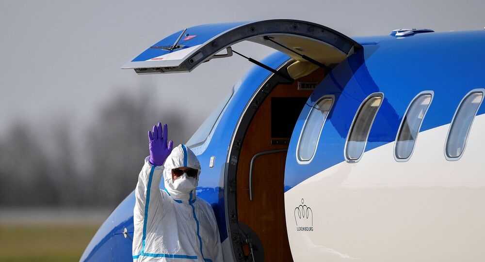A medical staff waves as a patient from France is transferred from an ambulance aircraft to an ambulance car at the airport in Dresden, as the spread of the coronavirus disease (COVID-19) continues in Dresden, Germany April 2, 2020.