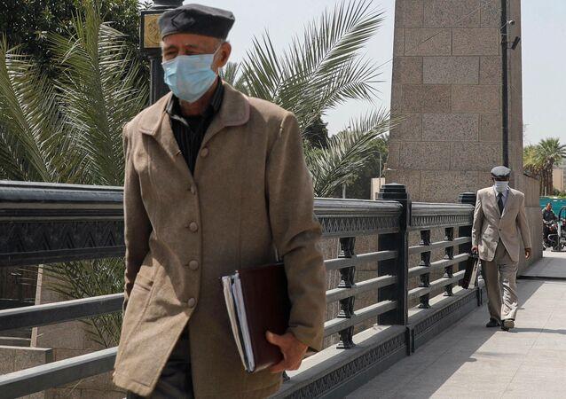 Older men wearing protective masks amid concerns over the coronavirus disease (COVID-19) walk on the Qasr el-Nil Bridge across the Nile river in Egyptian capital Cairo, Egypt March 31, 2020.