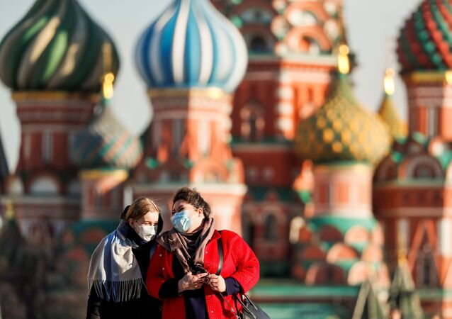Women with protective masks, widely used as a preventive measure against coronavirus disease (COVID-19), walk across Red Square near the St. Basil's Cathedral in central Moscow, Russia March 26, 2020
