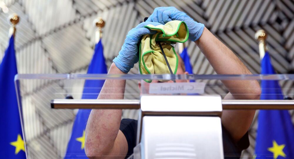 A man disinfects a desk before a news conference of European Council President Charles Michel after after EU heads of state held a videoconference to discuss measures for the coronavirus disease (COVID-19) in Brussels, Belgium, March 26, 2020.