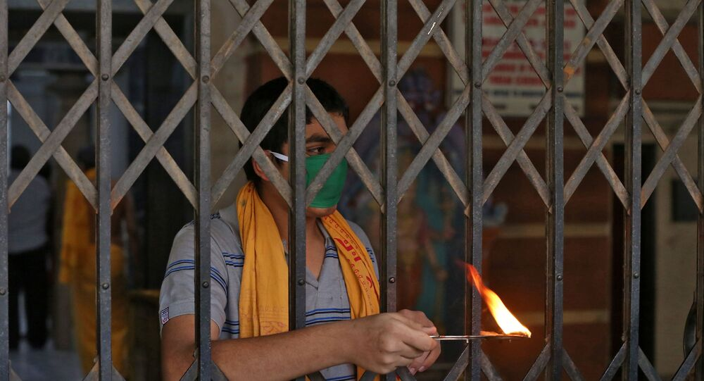 A Hindu priest performs a ritual known as Aarti to bless the devotees (not pictured) on the occasion of Ramnavmi festival at a temple during a 21-day nationwide lockdown to slow the spreading of coronavirus disease (COVID-19) in in Mumbai, India, April 2, 2020.