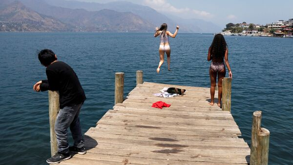 Backpacker and Spanish language student Lola Daehler, from the U.S., jumps into the water after she decided to stay in Guatemala, where she feels safer to confront the outbreak of coronavirus disease (COVID-19), in San Pedro La Laguna, Solola, Guatemala March 27, 2020 - Sputnik International