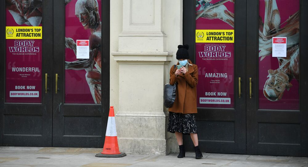 A woman looks at her phone whilst wearing a mask in Shaftesbury Avenue as the spread of the coronavirus disease (COVID-19) continues, London, Britain, March 31, 2020