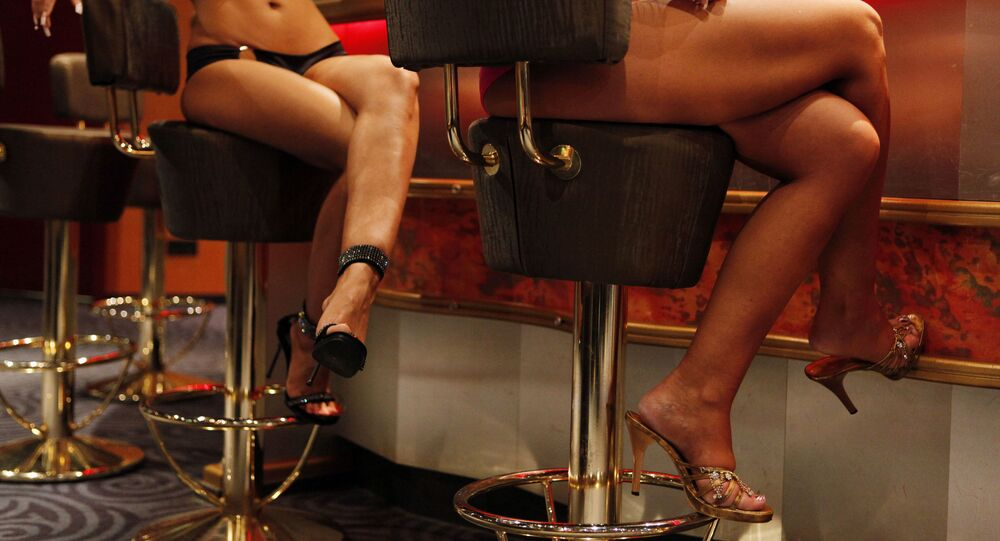 In this picture made Friday, May 8, 2009, Eva, left, and Dana, right (full names not given) pose inside the Artemis brothel in Berlin. Like so many other businesses, Europe's largest legalized prostitution industry is having to adapt to the economic downturn