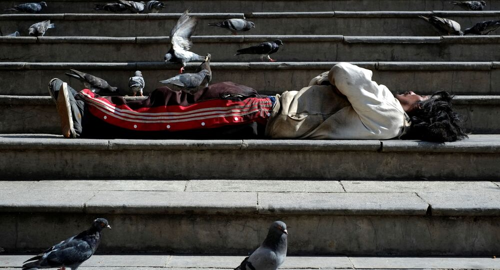 A homeless man surrounded by pigeons lies on the stairs at the Plaza San Francisco in La Paz, Bolivia, 8 March 2020
