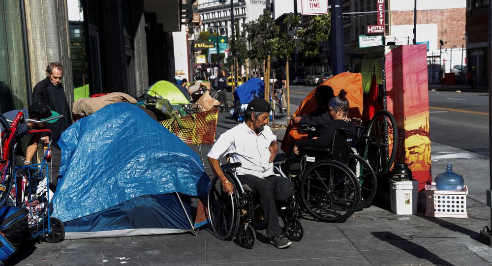 People line in a sidewalk filled with tents set up by the homeless, amid an outbreak of the coronavirus disease (COVID-19), in the Tenderloin district of San Francisco, California, U.S. April 1, 2020
