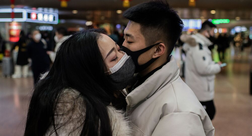 A couple, wearing protective masks, kisses goodbye as they travel for the Lunar New Year holidays, at Beijing West Railway Station in Beijing on January 24, 2020