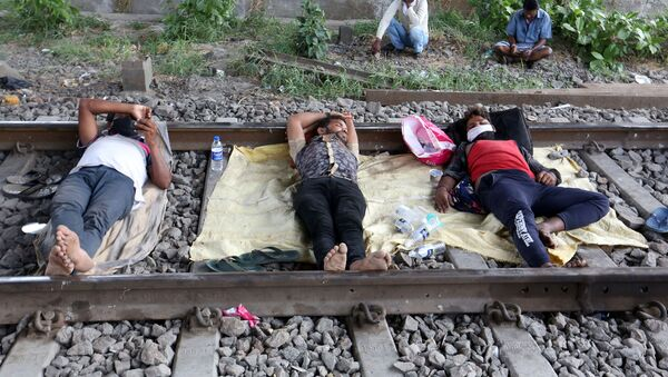 Migrant workers rest on a railway track during a 21-day nationwide lockdown to slow the spreading of coronavirus disease (COVID-19) in in Mumbai, India, April 2, 2020 - Sputnik International