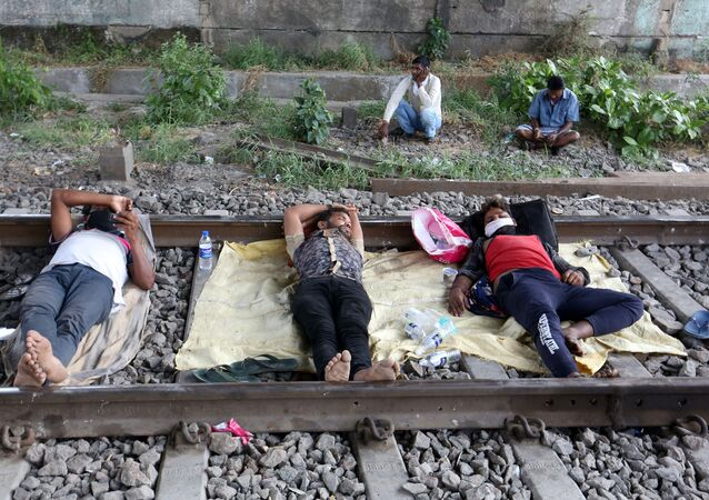 Migrant workers rest on a railway track during a 21-day nationwide lockdown to slow the spreading of coronavirus disease (COVID-19) in in Mumbai, India, 2 April 2020