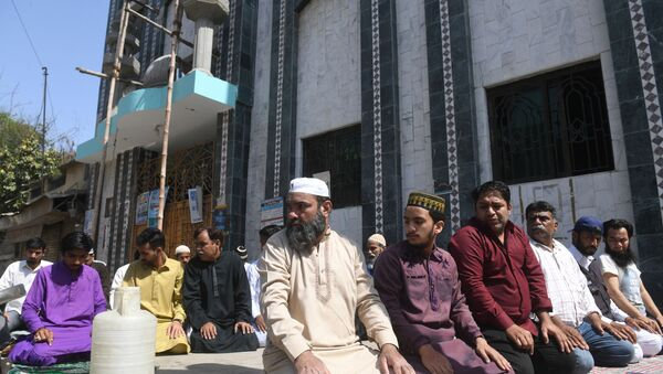 Muslim devotees offer Friday prayers outside a closed mosque alongside a street during a government-imposed nationwide lockdown as a preventive measure against the COVID-19 coronavirus, in Karachi on April 3, 2020. - Sputnik International