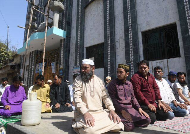 Muslim devotees offer Friday prayers outside a closed mosque alongside a street during a government-imposed nationwide lockdown as a preventive measure against the COVID-19 coronavirus, in Karachi on April 3, 2020.