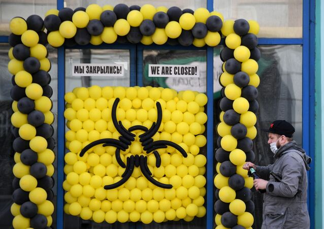 A man in a protective mask walks past a cafe in Moscow, closed due to the limited spread of coronavirus infection