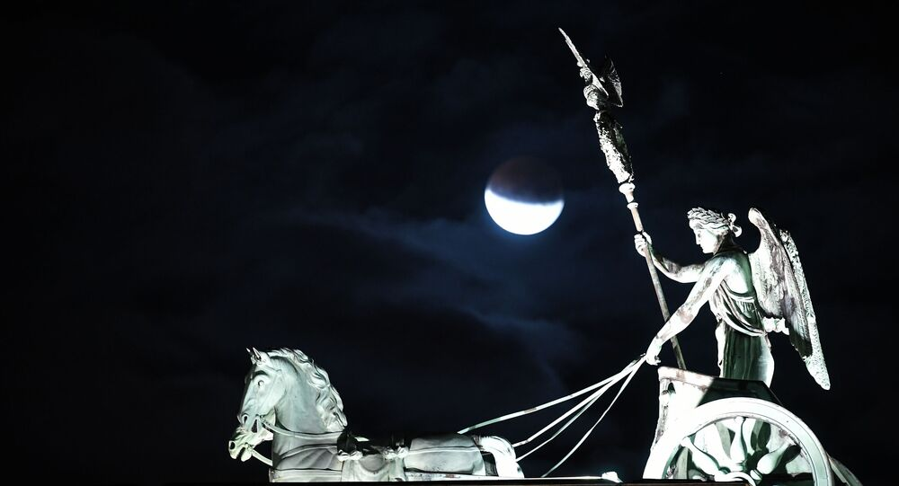 The moon is seen above the quadriga atop the Brandenburg Gate, Berlin's landmark