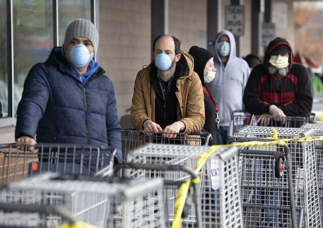 People wait to enter a supermarket that is limiting the number of customers at any one time, Friday, 3 April 2020, in Chelsea, Massachusetts