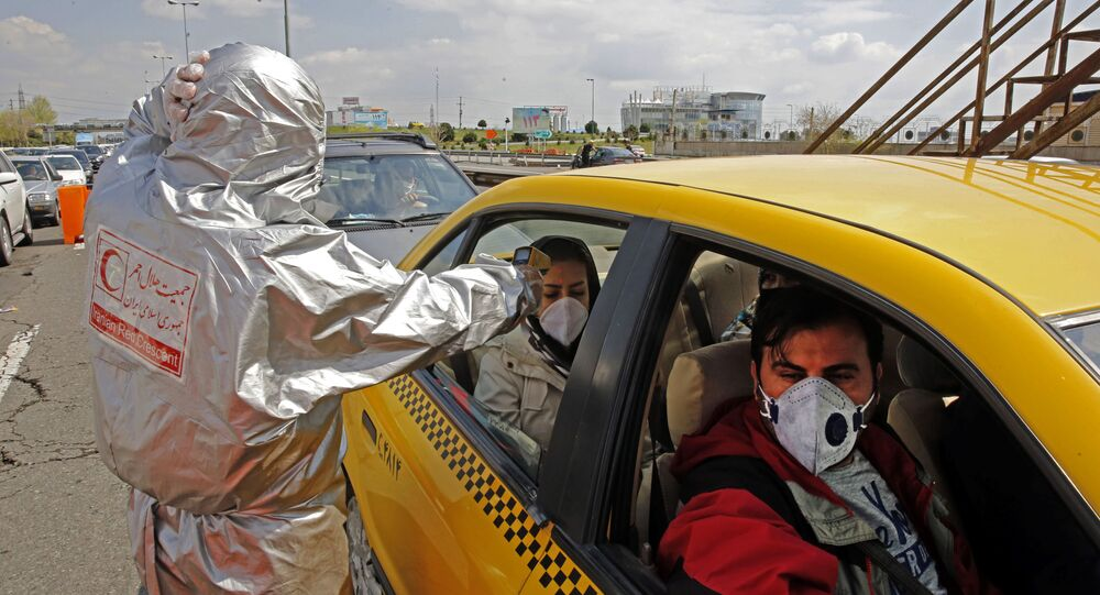 Members of the Iranian Red Crescent test people for coronavirus Covid-19 symptoms, as police blocked Tehran to Alborz highway to check every car following orders by the Iranian government, outside Tehran on March 26, 2020
