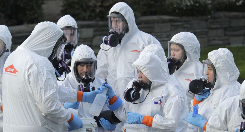 Workers from a Servpro disaster recovery team wearing protective suits and respirators are given supplies as they line up before entering the Life Care Center in Kirkland, Wash., to begin cleaning and disinfecting the facility, Wednesday, March 11, 2020