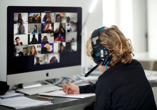 A student takes online classes at home using the Zoom APP