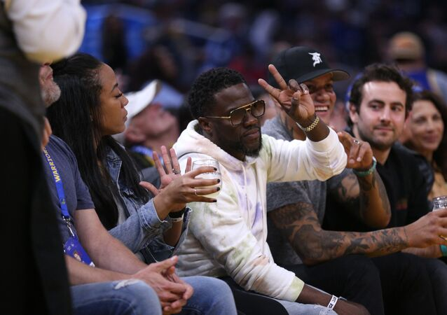 Actor and comedian Kevin Hart acknowledges the crowd during a timeout between the Golden State Warriors and the Philadelphia 76ers in the second quarter at the Chase Center