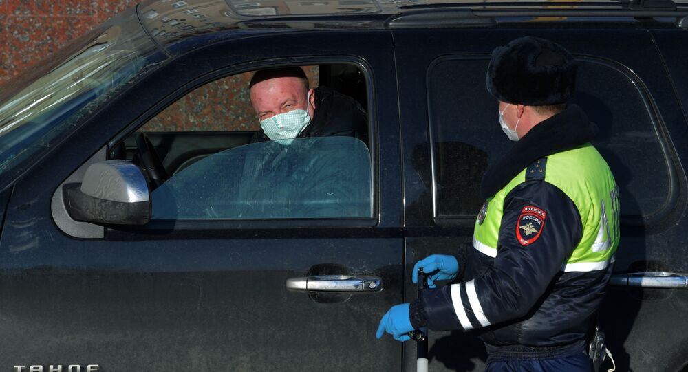 A Russian police officer speaks with driver amid coronavirus outbreak in Moscow