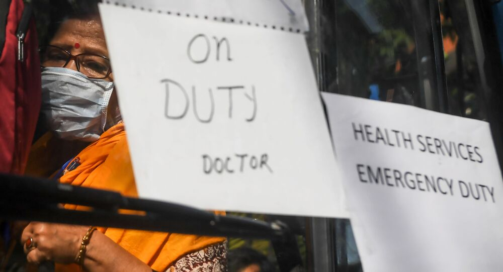 Governmental doctors board a bus to go to several districts as reinforcement in the city during a government-imposed nationwide lockdown as a preventive measure against the COVID-19 coronavirus, in Kolkata on March 27, 2020.