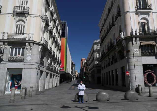 A pharmacist in protective gear stands in a deserted Puerta del Sol square