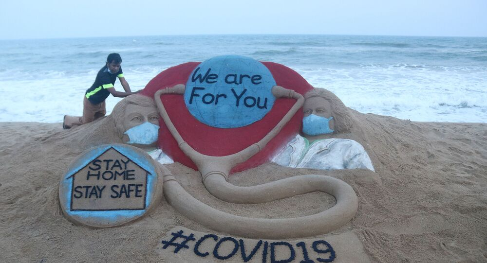 Indian artist Sudarsan Pattnaik puts some final touches as he makes a sand sculpture depicting doctors wearing protective facemasks with a message reading We are For You, Stay Home Stay Safe at Puri beach in Puri on April 3, 2020.