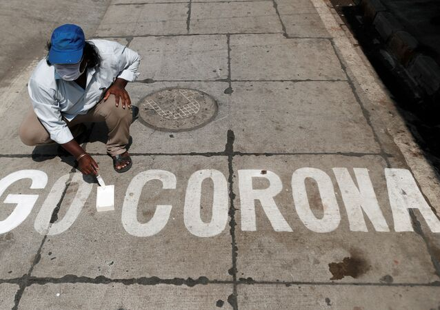 A man paints a message on a street after India ordered a 21- day nationwide lockdown to limit the spreading of coronavirus disease (COVID-19) in Mumbai, India March 28, 2020.