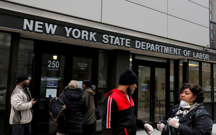 People gather at the entrance for the New York State Department of Labor offices, which closed to the public due to the coronavirus disease (COVID-19) outbreak in the Brooklyn borough of New York City, U.S.,  20 March 2020