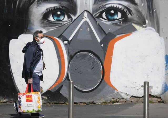 A man wearing a face mask walks past a graffiti