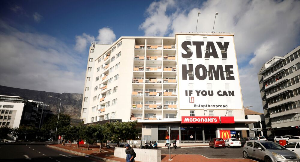 A man walks past a poster covering the side of a building ahead of a 21 day lockdown aimed at limiting the spread of coronavirus disease (COVID-19), in Cape Town