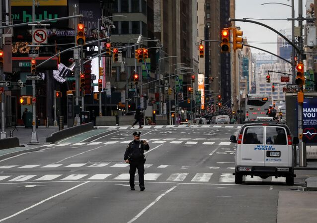 A New York City Police officer (NYPD) takes a selfie while in the middle of the street in an almost empty Times Square