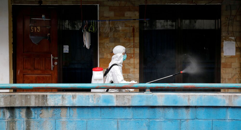 A Red Cross personnel wearing a protective suit sprays disinfectant along a corridor in a densely populated neighbourhood area, amid the spread of the coronavirus disease (COVID-19) in Jakart
