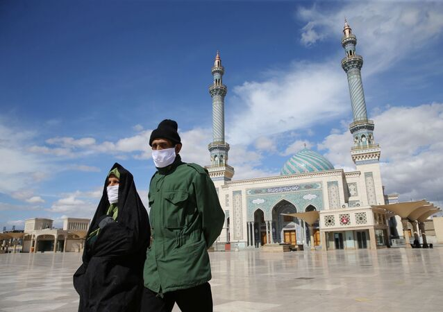 A couple wearing protective face masks, following the outbreak of coronavirus disease (COVID-19), walks on the street in Qom, Iran March 24, 2020. Picture taken March 24, 2020.