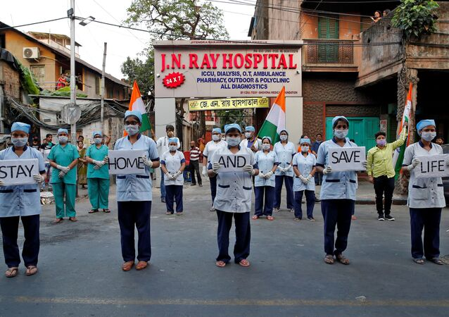 Medical staff members hold placards as they stand outside a hospital to show solidarity with people who are affected by the coronavirus disease (COVID-19), and with doctors, nurses and other healthcare workers from all over the world during a 21-day nationwide lockdown to slow the spreading of the disease, in Kolkata, India, April 5, 2020.