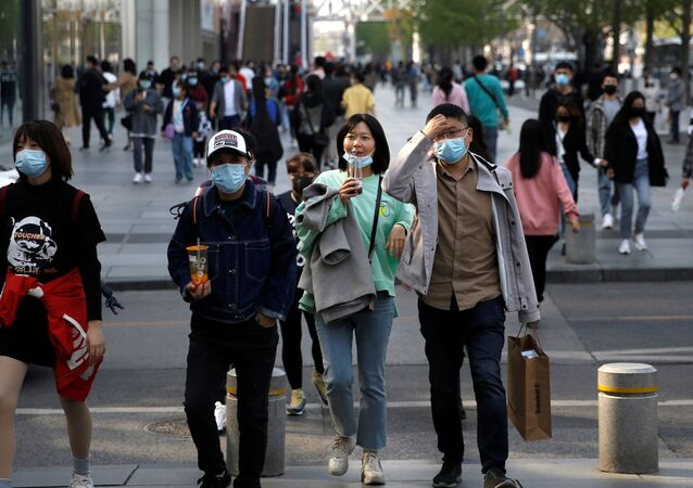 People wearing face masks are seen at a shopping area in Beijing, as the spread of the novel coronavirus disease (COVID-19) continues in the country, China April 6, 2020.