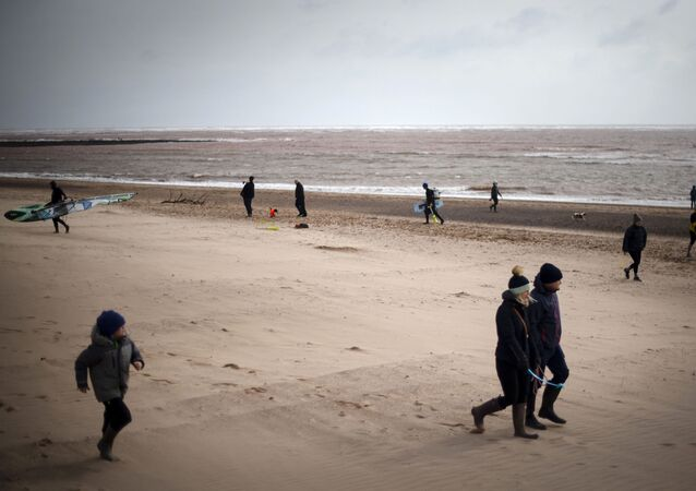 Walkers and kite surfers on Exmouth Beach despite the Government advising the public to reduce social interaction due to the coronovirus outbreak, in Exmouth, England, Sunday, March 22, 2020.