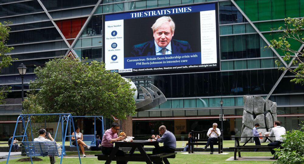 Workers take their lunch outdoors as a screen giving information about British Prime Minister Boris Johnson is seen on the background on the first day of circuit breaker measures to curb coronavirus (COVID-19) at the central business district in Singapore, April 7, 2020