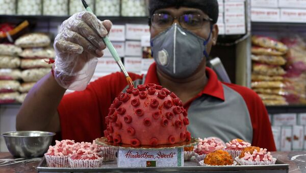 A confectioner applies finishing touches to a replica of coronavirus made out of sweets at a confectionary workshop during a 21-day nationwide lockdown to slow the spreading of coronavirus disease (COVID-19) in Kolkata, India, April 6, 2020 - Sputnik International