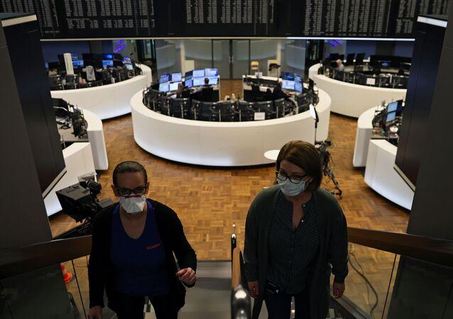 Women wear face masks at Frankfurt's stock exchange as markets react on the coronavirus disease (COVID-19), at the stock exchange in Frankfurt, Germany, 27 March 2020.