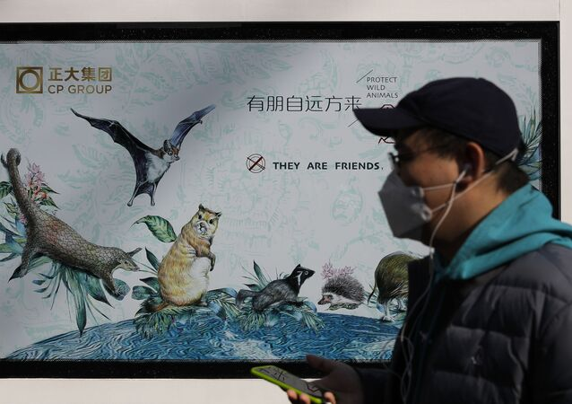 A man wearing a protective face mask walks by a propaganda poster promoting to protect wildlife animals after authorities crackdowns on wild animal markets following the coronavirus outbreak in Beijing, Wednesday, March 11, 2020.