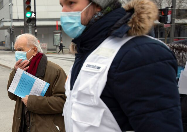 A man is escorted by healthcare workers to be tested as the city's public health unit holds a walk-in clinic testing for coronavirus disease (COVID-19) in Montreal, Quebec, Canada March 23, 2020.