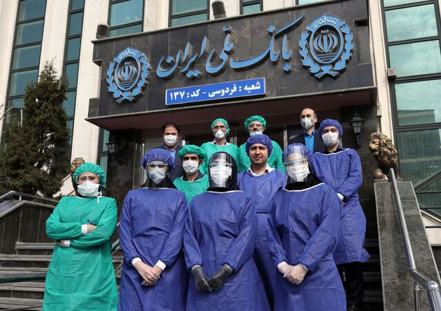 Bank employees wear protective face masks, following the outbreak of coronavirus, as they pose for a photo in Tehran, Iran March 17, 2020.