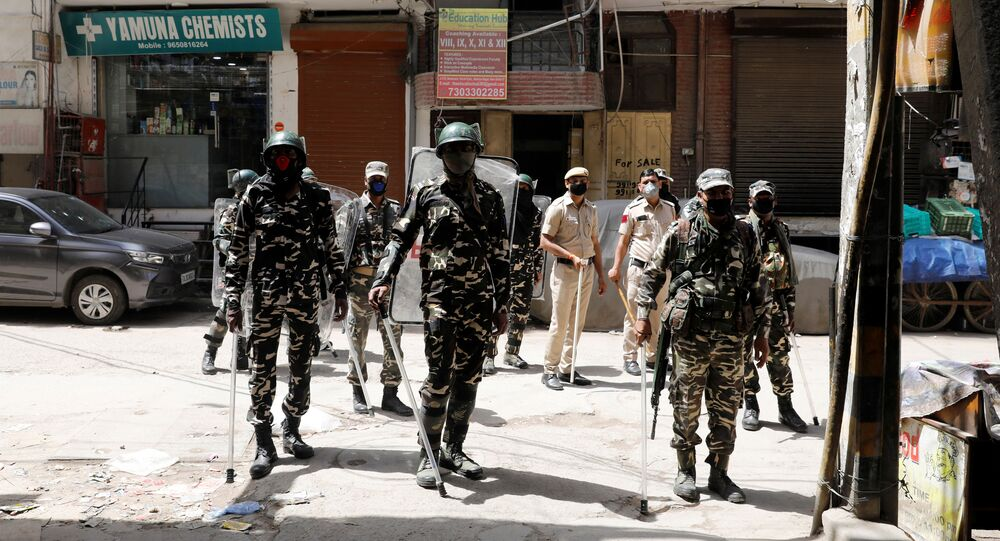 Paramilitary personnel and police officers stand guard on the street as India ordered a 21-day nationwide lockdown to limit the spreading of coronavirus disease (COVID-19), in New Delhi, India, March 25, 2020