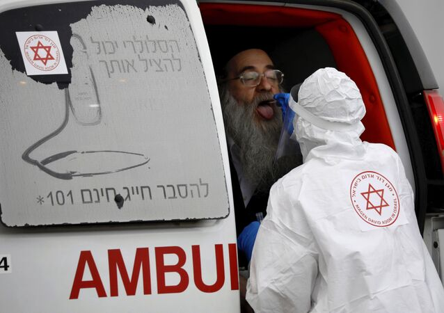 An Israeli medical worker wearing protective gear takes a swab from an ultra-Orthodox Jewish man for a coronavirus test, as part of the government's measures to stop the spread of the virus, in the Orthodox city of Bnei Brak, a suburb of Tel Aviv, Israel, Tuesday, March 31, 2020