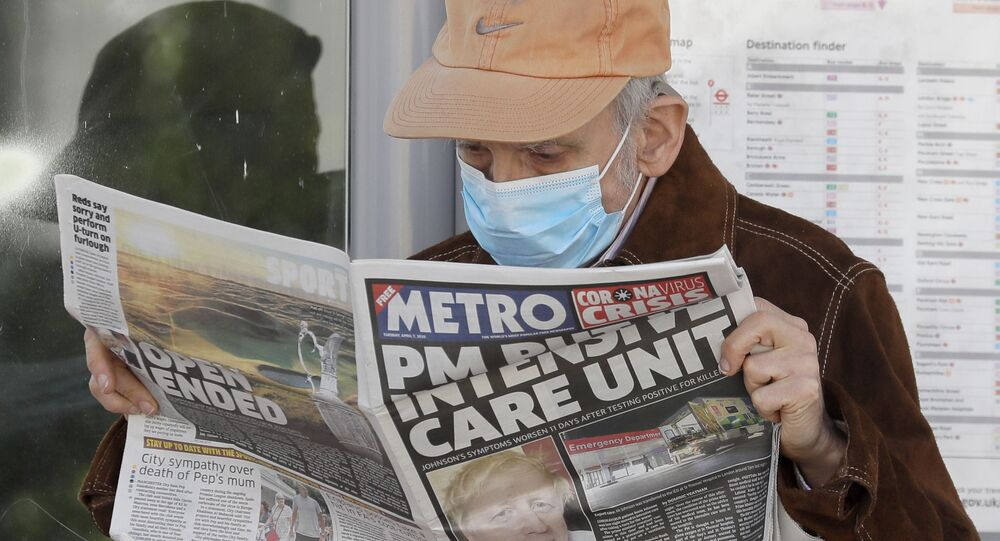 A man reads a newspaper with the headline: 'PM in intensive care', outside St Thomas' Hospital in central London as British Prime Minister Boris Johnson is in intensive care fighting the coronavirus in London, Tuesday, April 7, 2020.