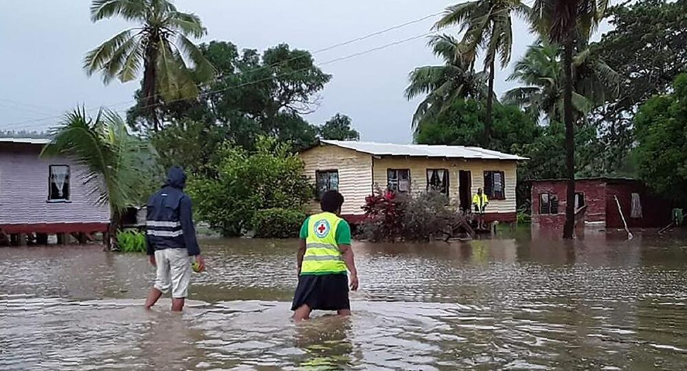 This handout photo taken and received on April 8, 2020 by the International Federation of Red Cross (IFRC) Pacific shows rescue workers making their way through a village during flooding caused by the Tropical Cyclone Harold in Nasolo in Fiji. - A deadly Pacific storm slammed into Fiji on April 8, tearing off roofs and flooding towns, after leaving a trail of destruction in the Solomon Islands and Vanuatu.