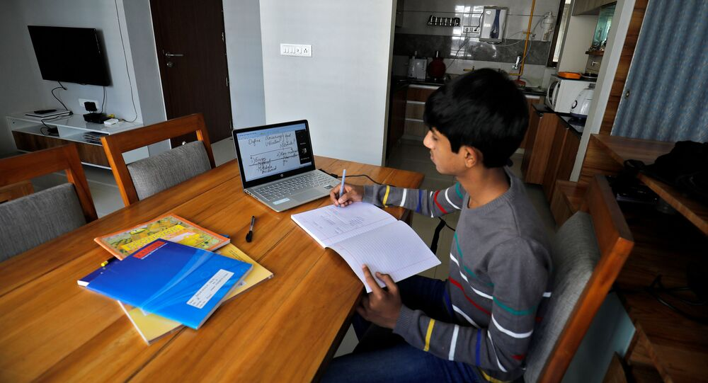 A student makes notes as he attends an online class at his home after Gujarat government ordered the closure of schools and colleges across the state amid coronavirus fears, in Ahmedabad, India, March 17,2020
