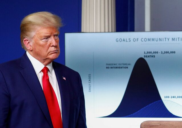 "U.S. President Donald Trump listens stands in front of a chart labeled ""Goals of Community Mitigation"" showing projected deaths in the United States after exposure to coronavirus as 1,500,000 - 2,200,000 without any intervention and a projected 100,000 - 240,000 deaths with intervention taken to curtail the spread of the virus during the daily coronavirus response briefing at the White House in Washington, U.S., March 31, 2020"