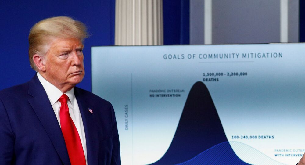 """U.S. President Donald Trump listens stands in front of a chart labeled """"Goals of Community Mitigation"""" showing projected deaths in the United States after exposure to coronavirus as 1,500,000 - 2,200,000 without any intervention and a projected 100,000 - 240,000 deaths with intervention taken to curtail the spread of the virus during the daily coronavirus response briefing at the White House in Washington, U.S., March 31, 2020"""